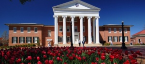 Photo of Lyceum at Ole Miss with red flowers in front of the building
